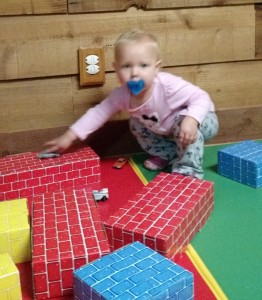 Little girl playing with cardboard bricks