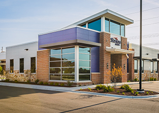 "Starion Bank chose Iconica to help expand its presence in Dane County. Iconica designed and constructed the Sun Prairie branch, completed in mid-November. The new building is just over 5,000 square foot and leaves plenty of room for their employee and customer's needs along with a drive-through, extended hours and a MoneyPass ATM. Iconica's team of architects, engineers, and construction managers joined forces with the Starion bankers to ensure a successful project, in addition to smoothly navigating the City's approval process. This synergy fully establishes the project from start to finish for the ultimate product. Some of the unique features of the bank are the actual dimensions. ""We had a tight place to work with and wanted to maximize the visibility and functional ability for staff and customers. Every inch of the building was thought through. The bank drive-through was an interesting feature to design around due to the spatial needs of the pneumatic carrier and making sure there was plenty of flow and parking for customers."" said Feller. Iconica worked closely with Tim Semmann, the Sun Prairie city planner on the project to make sure the intent of the general development plan for the area was fulfilled. Semmann said, ""The result is a unique and functional building that adds to the fabric of the Grand Avenue corridor for the benefit of customers and employees alike."" Iconica built Starion's first bank in Wisconsin in 2006 in Middleton. They opened a branch in Sun Prairie in 2013 in a temporary location adjacent to the new facility we designed. They acquired a third Dane County location in Monona in 2015. Starion is a family owned community bank based in Bismarck, North Dakota, with 12 additional banks throughout the state."
